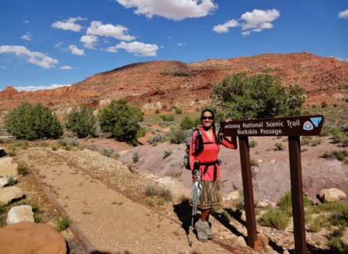 Woman with a backpack stands next to a sign that says Arizona National Scenic Trail