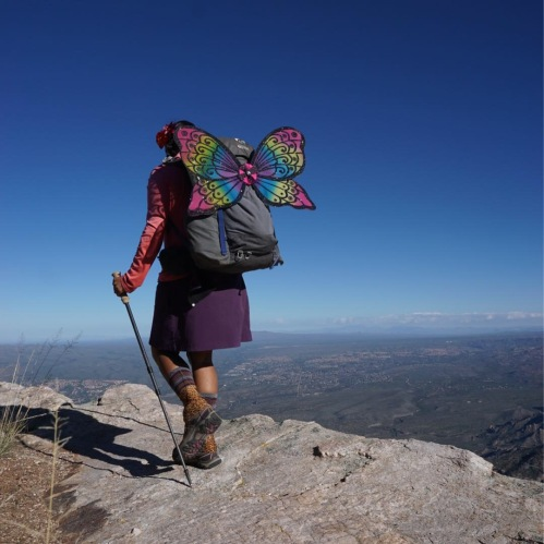 A woman in a skirt carries a large backpack with butterfly wings on top of a mountain